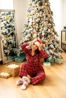 Mädchen, das hörner aus karamellen des neuen jahres tut und weihnachten feiert. auf dem hintergrund verzierter weihnachtsbaum mit geschenken.