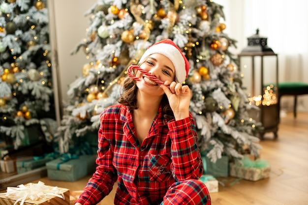 Mädchen, das hörner von den karamellen des neuen jahres hält und weihnachten feiert. auf dem hintergrund geschmückter weihnachtsbaum mit geschenken.