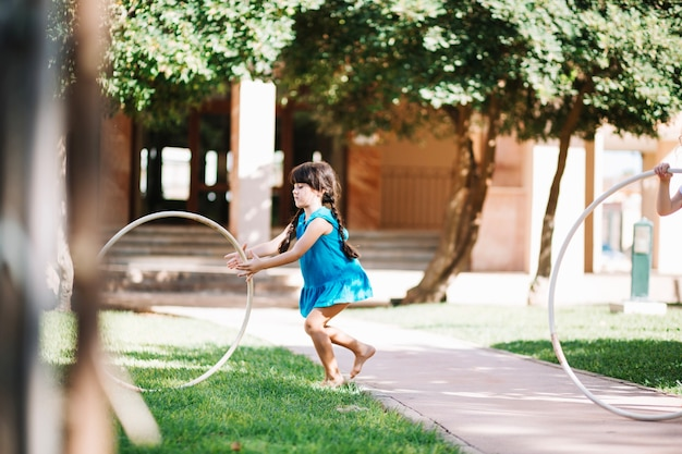 Mädchen, das hula-hoop auf gras rollt