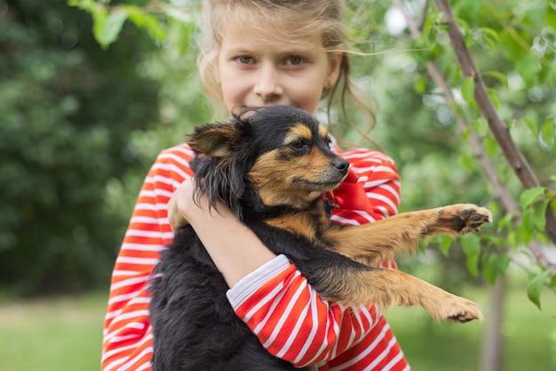 Mädchen, das hund im freien, freundschaft und liebe zwischen kleinem besitzer und haustier umarmt