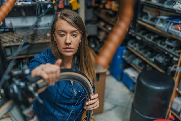 Mädchen, das ihr fahrrad repariert