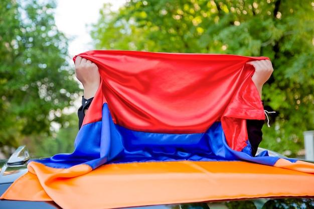 Mädchen, das ihr gesicht beschönigt und armenische flagge in straße mit grünem naturhintergrund hält