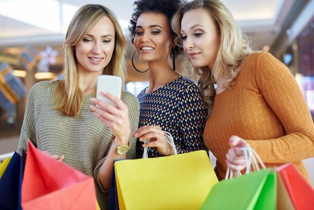 Mädchen, das ihr handy während des einkaufens benutzt