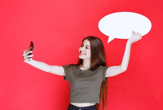 Mädchen, das ihr selfie mit einer ovalen infotafel nimmt.