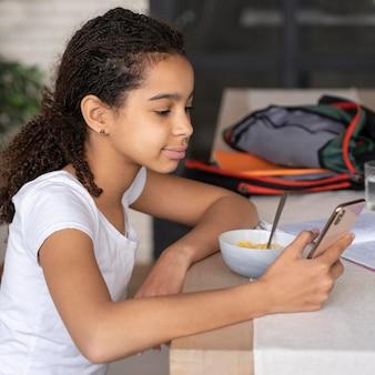 Mädchen, das ihr telefon beim frühstück überprüft