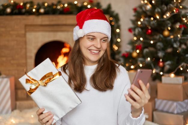 Mädchen, das ihr weihnachtsgeschenk durch videoanruf zeigt, weiße box mit goldenem band haltend, hat gespräch über smartphone, im wohnzimmer sitzend mit weihnachtsdekoration.
