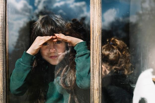 Mädchen, das ihre augen beim schauen durch glasfenster abschirmt