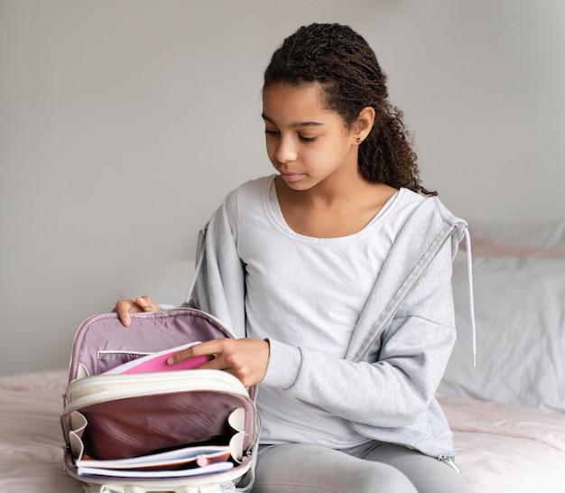 Mädchen, das ihre bücher in den rucksack legt