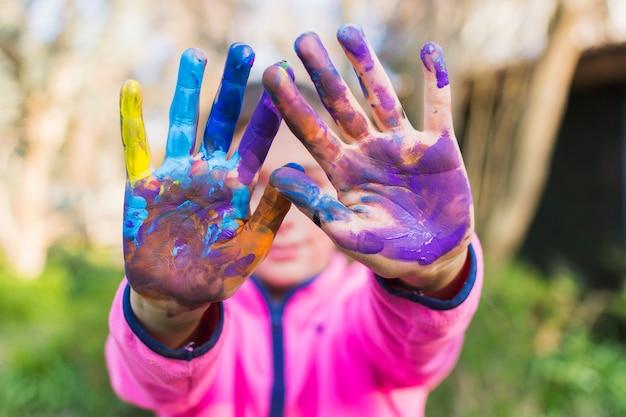 Mädchen, das ihre bunten gemalten hände zeigt