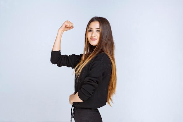 Mädchen, das ihre faust und stärke zeigt. foto in hoher qualität