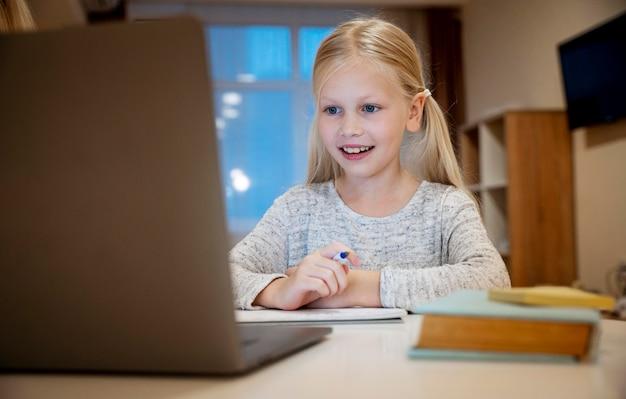 Mädchen, das ihre hausaufgaben auf laptop-konzept macht