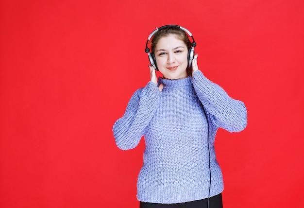 Mädchen, das ihre kopfhörer trägt, um die musik zu hören.