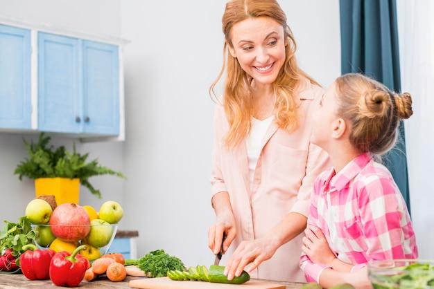 Mädchen, das ihre lächelnde mutter schneidet die gurke mit messer in der küche betrachtet