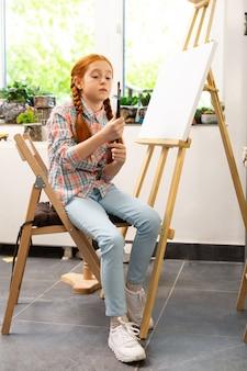 Mädchen, das ihre malpinsel hält, bevor es in der kunstschule malt