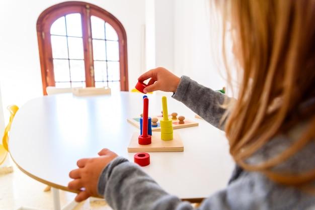 Mädchen, das ihre manuelle fingerfertigkeit mit einem sensorischen material von farben entwickelt.