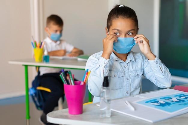 Mädchen, das ihre medizinische maske in der klasse aufsetzt