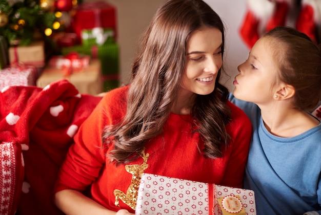 Mädchen, das ihre mutter an weihnachten küsst