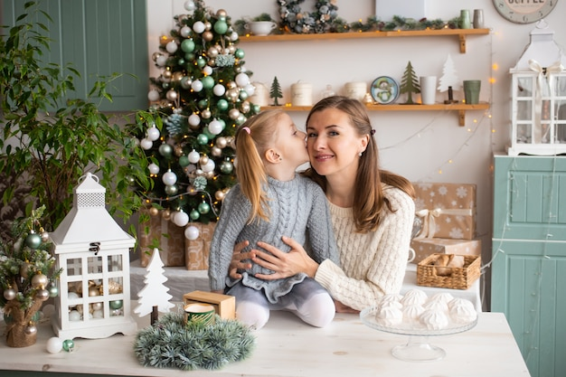 Mädchen, das ihre mutter beim auf küchentisch im weihnachten zu hause sitzen küsst.