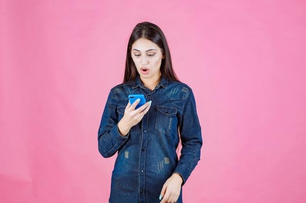 Mädchen, das ihre nachrichten oder social-media-plattform an ihrem smartphone überprüft