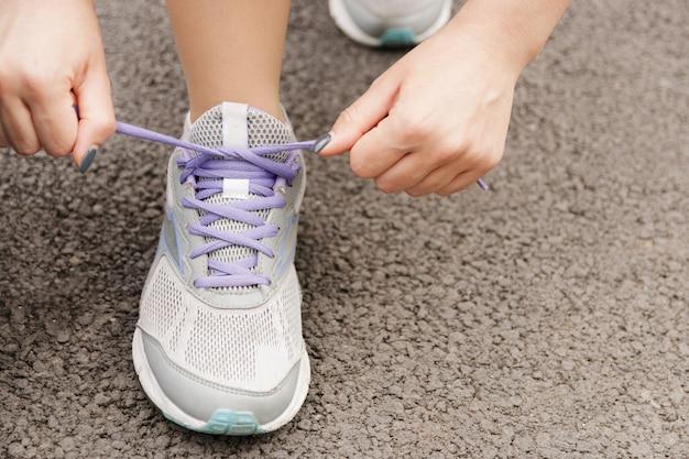 Mädchen, das ihre schuhe schnürt, bevor sie draußen, trainingswellneßkonzept laufen