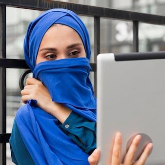 Mädchen, das ihre tablette betrachtet, während sie ihren mund mit einem hijab bedeckt