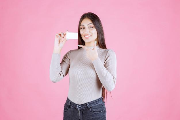 Mädchen, das ihre visitenkarte hält und mit dem finger darauf zeigt