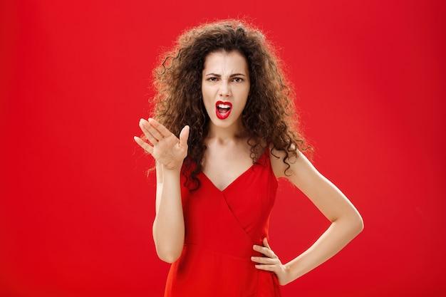 Mädchen, das ihre wut den mitarbeitern satt hat, die von unangemessenem verhalten satt sind und sich beschweren, sauer und unzufrieden zu stehen, mit der handfläche zu gestikulieren und die hand auf der hüfte über rotem hintergrund zu halten.