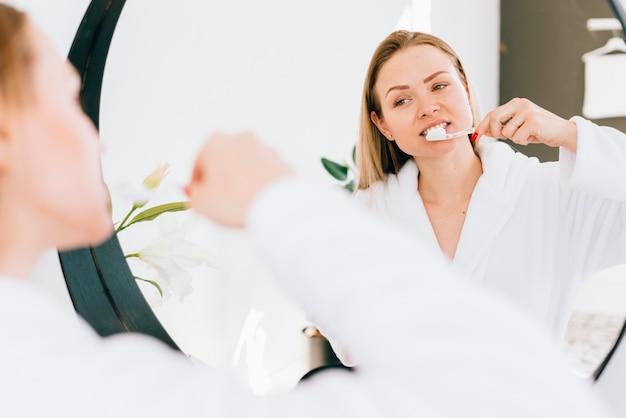 Mädchen, das ihre zähne am badezimmer putzt