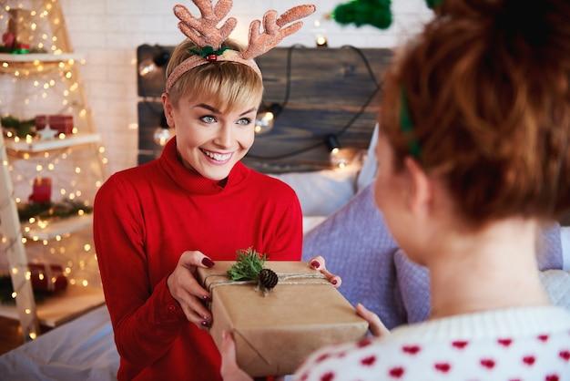 Mädchen, das ihrem freund weihnachtsgeschenk gibt