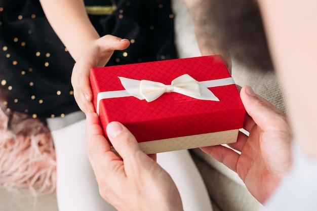 Mädchen, das ihrem vater am vatertag oder am geburtstag ein geschenk gibt. belohnung in einer roten geschenkbox von einem dankbaren und liebevollen kind bis zum besten vater aller zeiten.
