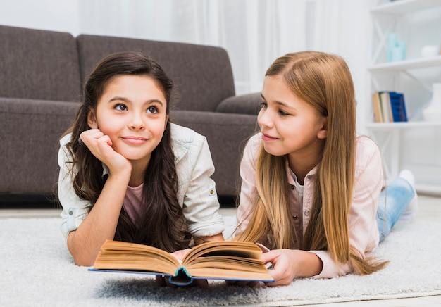 Mädchen, das ihren durchdachten freund während lesebuch im wohnzimmer betrachtet
