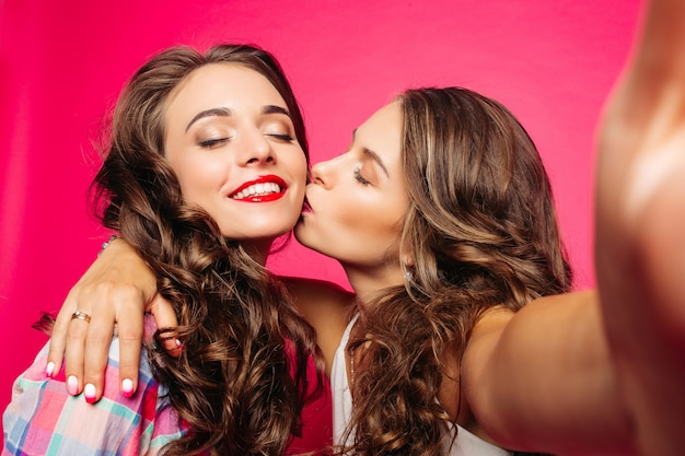 Mädchen, das ihren freund beim machen von selfie küsst.