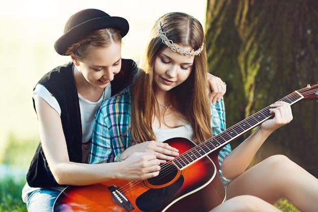 Mädchen, das ihren freund lehrt, gitarre im park zu spielen