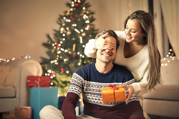 Mädchen, das ihren freund mit einem weihnachtsgeschenk überrascht