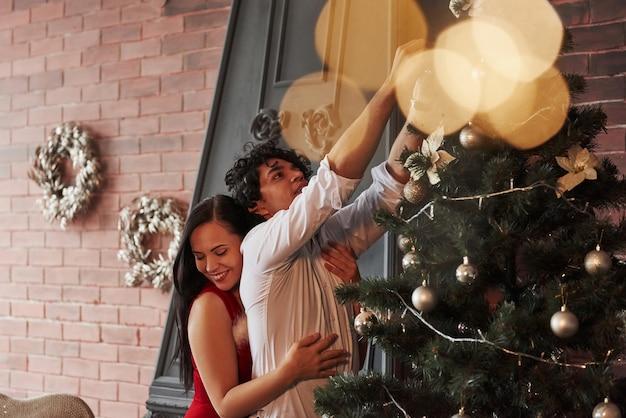 Mädchen, das ihren freund mit liebe umarmt. romantisches paar, das weihnachtsbaum im zimmer mit brauner wand und kamin verkleidet.