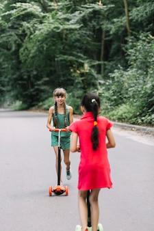Mädchen, das ihren freund reitroller auf straße betrachtet