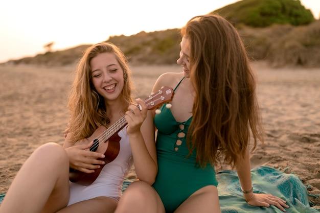 Mädchen, das ihren freund spielt ukulele am strand betrachtet