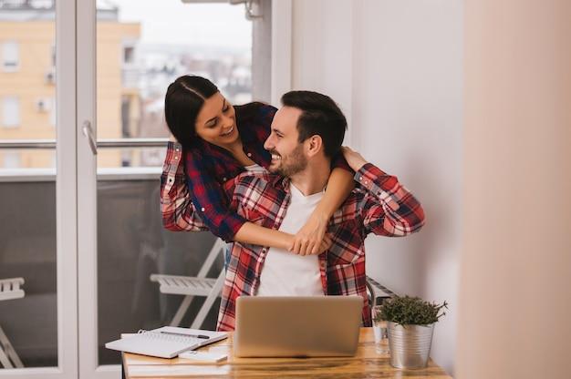 Mädchen, das ihren freund umarmt, während er zu hause büro bearbeitet