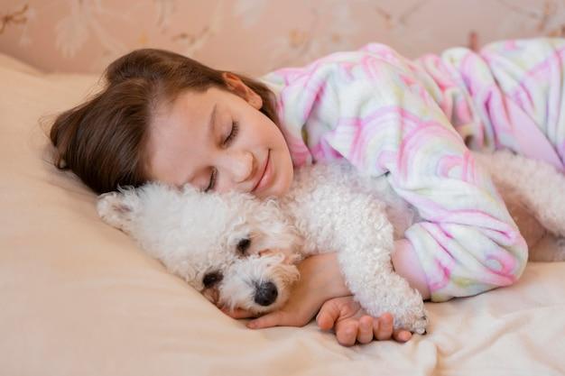 Mädchen, das ihren hund im bett beim schlafen umarmt