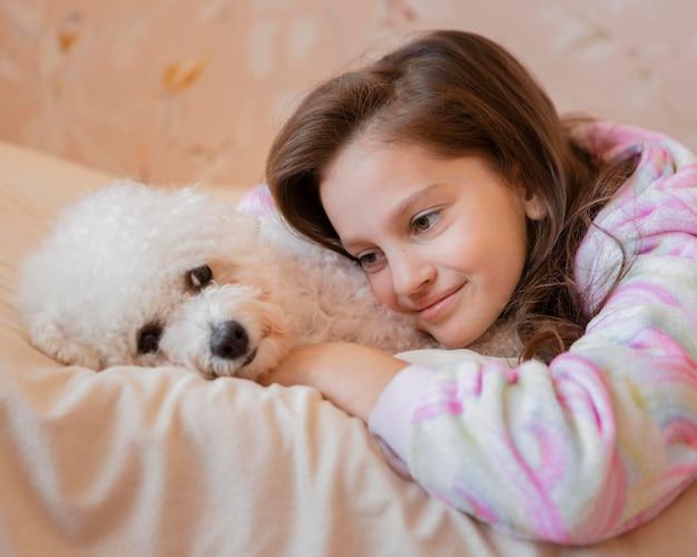 Mädchen, das ihren hund im bett umarmt