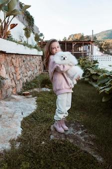 Mädchen, das ihren hund in ihren armen lange schuss hält