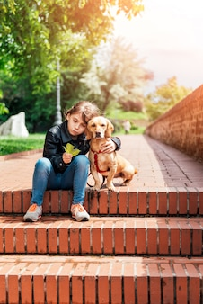 Mädchen, das ihren hund umarmt und auf der treppe sitzt