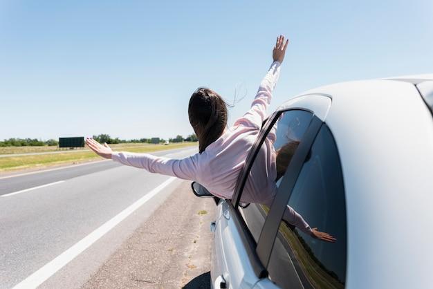 Mädchen, das ihren kopf aus dem fensterauto heraus setzt