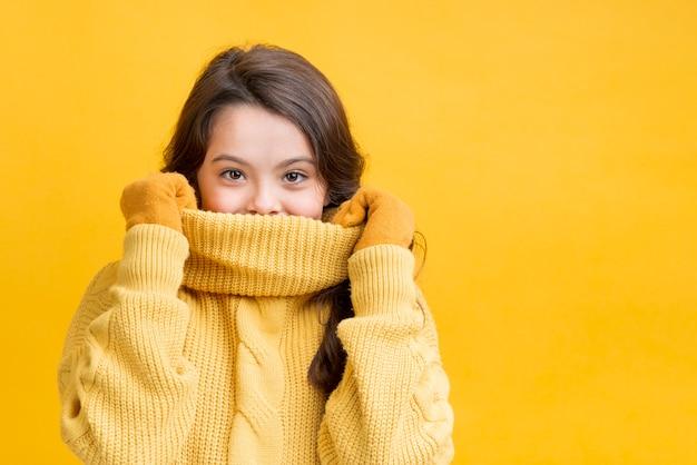 Mädchen, das ihren mund mit ihrer strickjacke bedeckt
