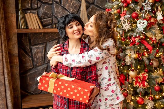 Mädchen, das ihrer freundin ein weihnachtsgeschenk gibt. mädchen, das ihren freund nahe weihnachtsbaum küsst.
