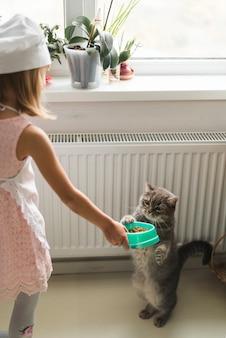 Mädchen, das ihrer katze nahrung gibt