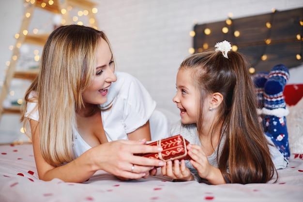 Mädchen, das ihrer mutter weihnachtsgeschenk gibt