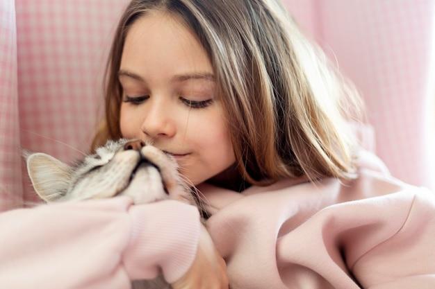 Mädchen, das ihrer schönen katze zischt