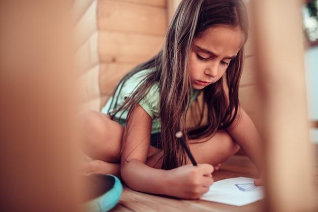 Mädchen, das im baumhaus spielt und mit farbigen bleistiften zeichnet