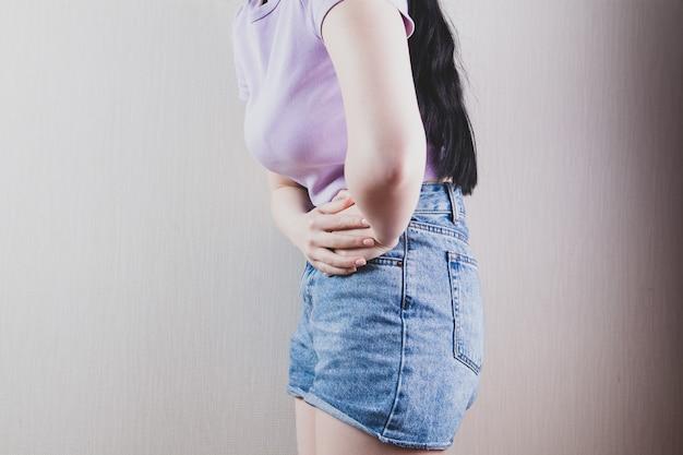 Mädchen, das im bett liegt, das unter magenschmerzen leidet
